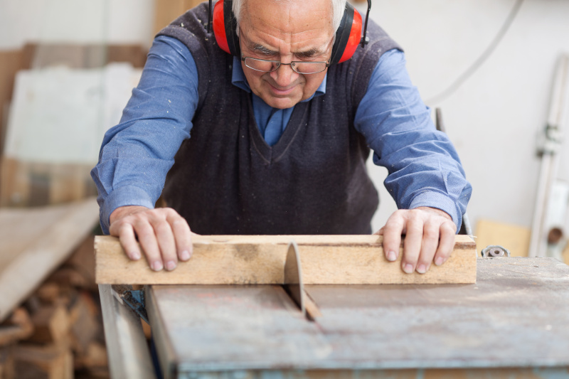 Mann zersägt Holz mit Kreissäge