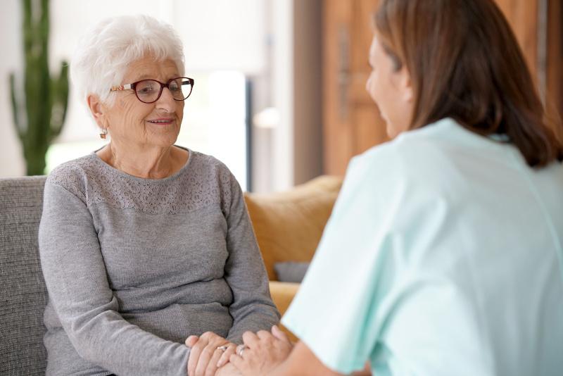 Pflegerin redet mit älterer Frau