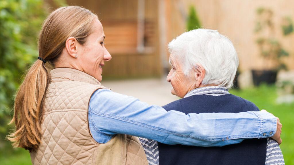 Betreuung Demenz, Frau hält Rentnerin im Arm, Verständnis demenzerkrankte